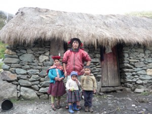 A family from the high Andean community of Panticalle, poses in front of their house