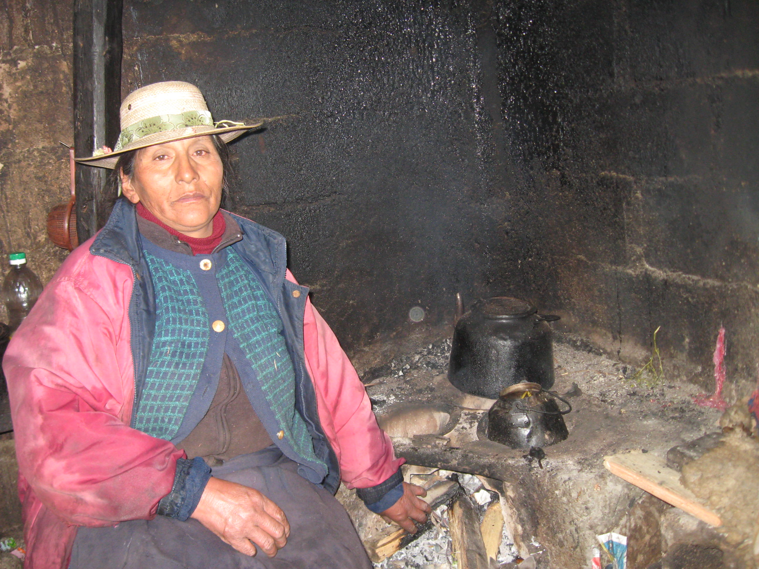 Susanna, a resident at the Abra Malaga pass, located at over 4200m above sea level, next to her existing stove. Note the black stain on the wall behind the stove where the smoke currently escapes.